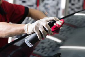 Spray ample amounts of glass cleaner over the windshield