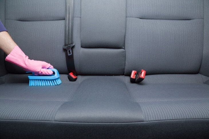 Cleaning a car's textile seats with professionally brush